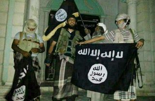 A picture taken with a mobile phone early on May 24, 2014 shows Al-Qaeda militants posing with Al-Qaeda flags in front of a museum in Seiyun, second Yemeni city of Hadramawt province, after launching a massive pre-dawn assault that killed at least 15 soldiers and police. The assault in Hadramawt, a jihadist stronghold that has seen large-scale attacks on the army in the past, came as troops pressed a month-old ground offensive against Al-Qaeda in Abyan and Shabwa provinces to the west. AFP PHOTO / STR (Phot