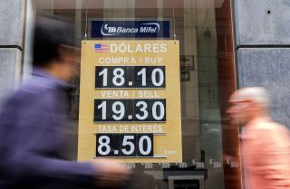 A view of an exchange rate for U.S. dollars in the window of a Mexican bank.
