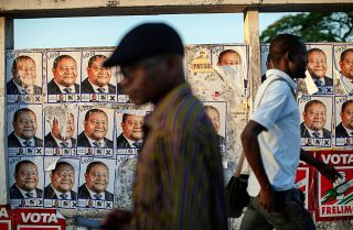 Posters for Renamo's presidential candidate, Ossufo Momade, line a wall ahead of Mozambique's Oct. 15 polls.