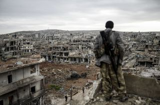 A man stands on top of a building overlooking the destryoed town of Kobane, Syria.