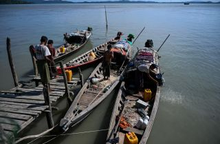 This photo taken on Oct. 2, 2019, shows fishermen boarding their boats at a small jetty on Made Island off Kyaukphyu in Myanmar's Rakhine state.