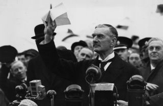 British Prime Minister Neville Chamberlain arrives at Heston airport outside London in 1938 with the Munich Pact he and Germany's Adolf Hitler signed.