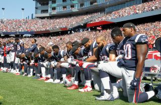 Members of the New England Patriots kneel during the national anthem before a game in Massachusetts.