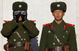 Soldiers in North Korea survey the South from across the Demilitarized Zone in late 2011.