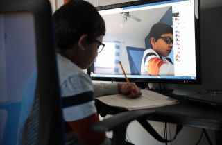 Seven-year-old Hamza Haqqani, a 2nd grade student at Al-Huda Academy, uses a computer to participate in an online class with his teacher and classmates at his home in Bartlett, Illinois, on May 1, 2020. Al-Huda Academy has had to adopt an e-learning program to finish the year after all schools in the state were forced to cancel classes to curb the spread of COVID-19.