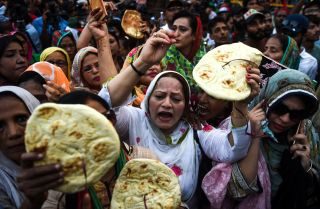 Activists from the Pakistan People's Party hold bread aloft in a protest against Prime Minister Imran Khan's government budget on June 23, 2019, in the southern city of Karachi.