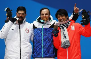 Finnish snowboarder Matti Suur-Hamari, center, celebrates his gold medal win with silver medalist Keith Gabel of the United States, left, and Gurimu Narita of Japan.