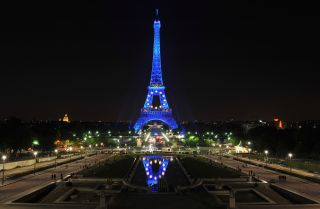 The Eiffel tower is lit with symbols of the European Union, including the stars and blue color that make up the bloc's flag.