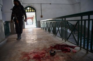 A policeman responds to a Dec. 1 terrorist attack at the Agricultural Training Institute in Peshawar, Pakistan, capital of Khyber-Pakhtunkhwa province.