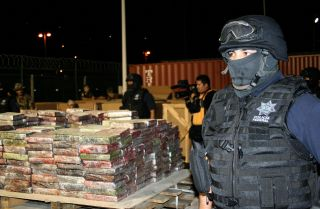 Police guard stacks of seized cocaine.