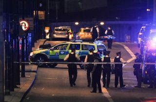 Police officers walk at night along the London Bridge after a terrorist attack.
