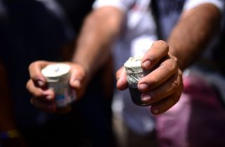 A protestor in Nicaragua shows off two homemade bombs.