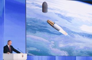 This photo shows Russian President Vladimir Putin with an image of a strategic missile
