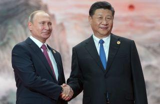 Vladimir Putin shakes hands with Xi Jinping