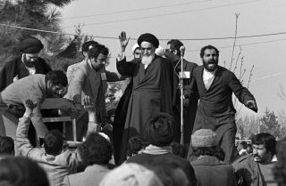 In this 1979 file image, Ayatollah Ruhollah Khomeini waves to supporters during his return to Tehran from exile in France.