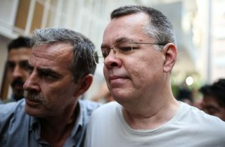 U.S. pastor Andrew Craig Brunson (R), escorted by Turkish plainclothes police officer,s arrives in Izmir, Turkey, July 25.