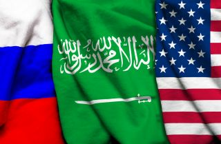 An impage shows the Russian, Saudi Arabian and U.S. flags from left to right.