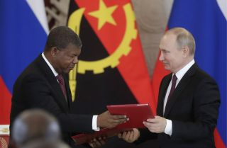 Angolan President Joao Lourenco, left, and Russian President Vladimir Putin exchange documents during a signing ceremony in Moscow on April 4, 2019.