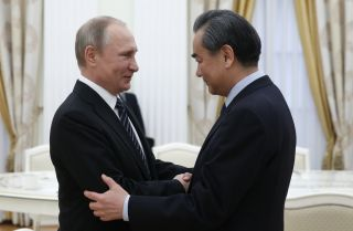 Russian President Vladimir Putin, pictured here with Chinese Foreign Minister Wang Yi, has reason to collaborate with Beijing in Kyrgyzstan.