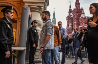 Visitors wait by security personnel in front of the entrance of a department store near Red Square in Moscow on Sept. 13.