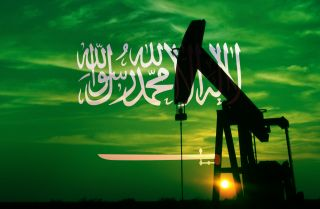 An image of a Saudi flag overlaying an oil pumpjack.