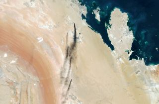 This satellite photo shows smoke pouring from two Saudi oil production facilities hit in Sept. 14 attacks.