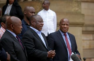 South African President Cyril Ramaphosa (center) addresses the media in Pretoria after concluding a meeting with various business and political leaders on matters relating to the COVID-19 outbreak on March 22, 2020.