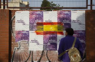 A woman in Seville, Spain, looks at election posters for the United We Can (Unidas Podemos) party on April 22, 2019.