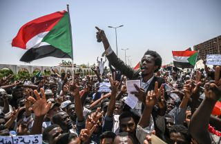 Sudanese protesters wave national flags and chant slogans during a sit-in outside the army headquarters in the capital of Khartoum, April 26.