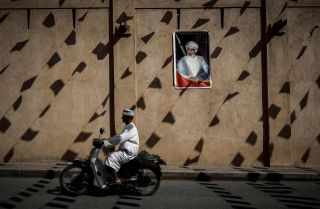 A man rides a motorcycle past a wall of the Nizwa fort bearing a portrait of Omani Sultan Qaboos bin Said in February.