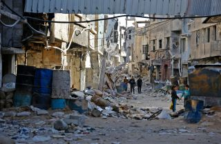 People walk amid rubble of destroyed buildings in a street in the Tadamun neighborhood near the Palestinian Yarmuk camp in southern Damascus on Nov. 3, 2018.