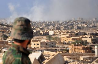 A member of the pro-Syrian government forces watches as smoke rises from buildings in the eastern Syrian city of Deir el-Zour after a Russian airstrike targeted Islamic State militants.