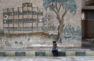 A child sits in front of the bullet-riddled wall of a former school in Syria's eastern Ghouta, a rebel-held area on the outskirts of Damascus, on Jan. 5, 2016.