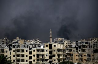 Buildings in a neighborhood in the western Raqqa smolder as the Syrian Democratic Forces fight the Islamic State.