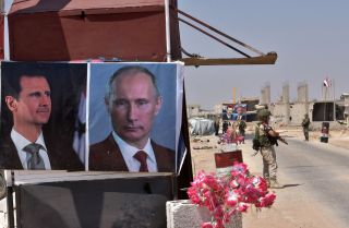 Posters of Syrian President Bashar al Assad and of Russian President Vladimir Putin adorn a kiosk at a border crossing in eastern Idlib province.