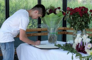A man signs a condolence book at the U.S. Embassy in Dushanbe, Tajikistan, for the four bicyclists killed in a terrorist attack on July 29, 2018.