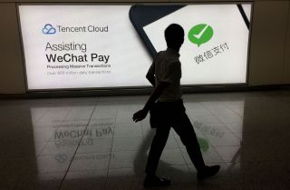 In this August 2017 photo, a man walks past an ad in Hong Kong's international airport for the social media platform WeChat, which is owned by China's Tencent.