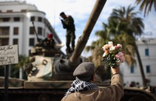 A demonstrator offers flowers to soldiers on Jan. 21, 2011, in Tunis during a three-day period of mourning for the people who died during the country's revolution.