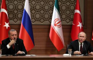 In this photograph, Presidents Recep Tayyip Erdogan (left) of Turkey and Vladimir Putin of Russia speak during a tripartite summit on Syria in April 2018.