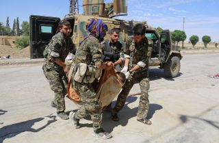 Members of the U.S.-backed Kurdish People's Protection Units carry a wounded Kurdish fighter to a field hospital near the northern Syrian village of Raqqa Samra on June 21, 2017.