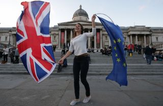 A woman waves the British and EU flags at a protest about the terms of the Brexit held in London's Trafalgar Square on Sept. 13, 2017.