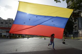 In the streets of Caracas, a girl plays near a Venezuelan flag in July 2017.