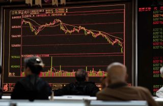 Investors watch stock price movements at a securities company in Beijing on Oct. 12.