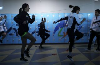 Members of the Korean women's ice hockey team warms up before a match days before the 2018 Winter Olympics, where they will compete as a unified team for the first time in Olympic history.