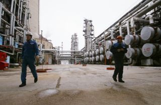 Workers walk through an oil refinery.