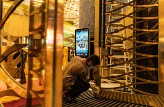 An employee cleans a door at the entrance of the Grand Lisboa Hotel in Macau on Feb. 5, 2020.