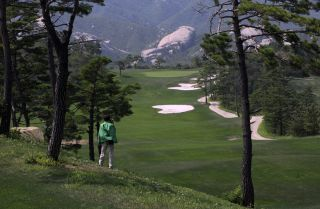 This photo shows a Chinese tourist photographing the derelict golf course at the shuttered Mount Kumgang resort in North Korea.