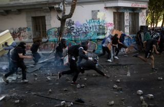 This photo shows protesters in Santiago, Chile, running from riot police on Nov. 19, 2019.