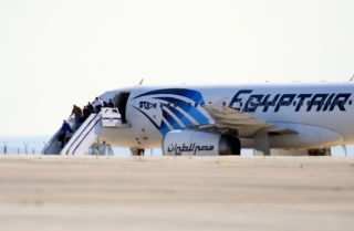 Passengers exit an EgyptAir Airbus A-320 sitting on the tarmac of Larnaca airport after it was hijacked and diverted to Cyprus on March 29, 2016.