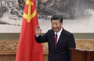Chinese President Xi Jinping waves after introducing the new members of China's top decision-making body, the Communist Party's Politburo Standing Committee, on Oct. 25 in Beijing.